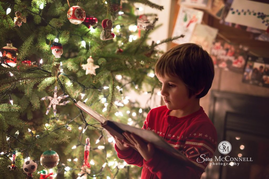 young boy reading a book at the Christmas tree