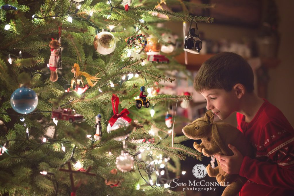 child looking at ornaments on the tree