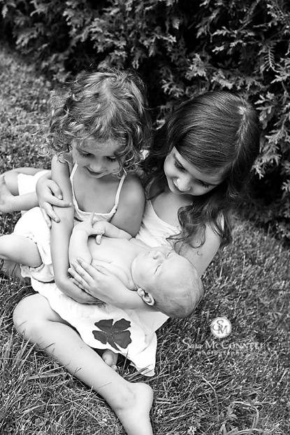 Children holding new baby brother