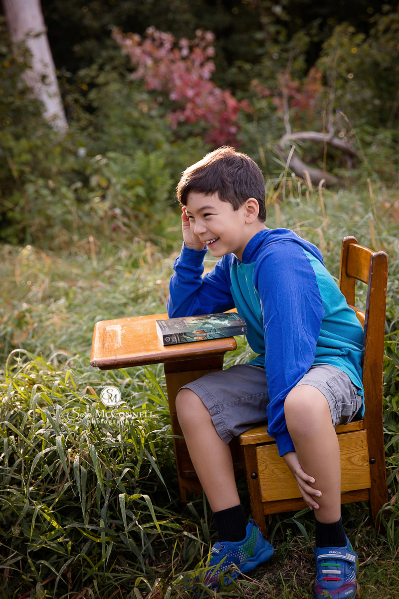 child sitting at school desk outside