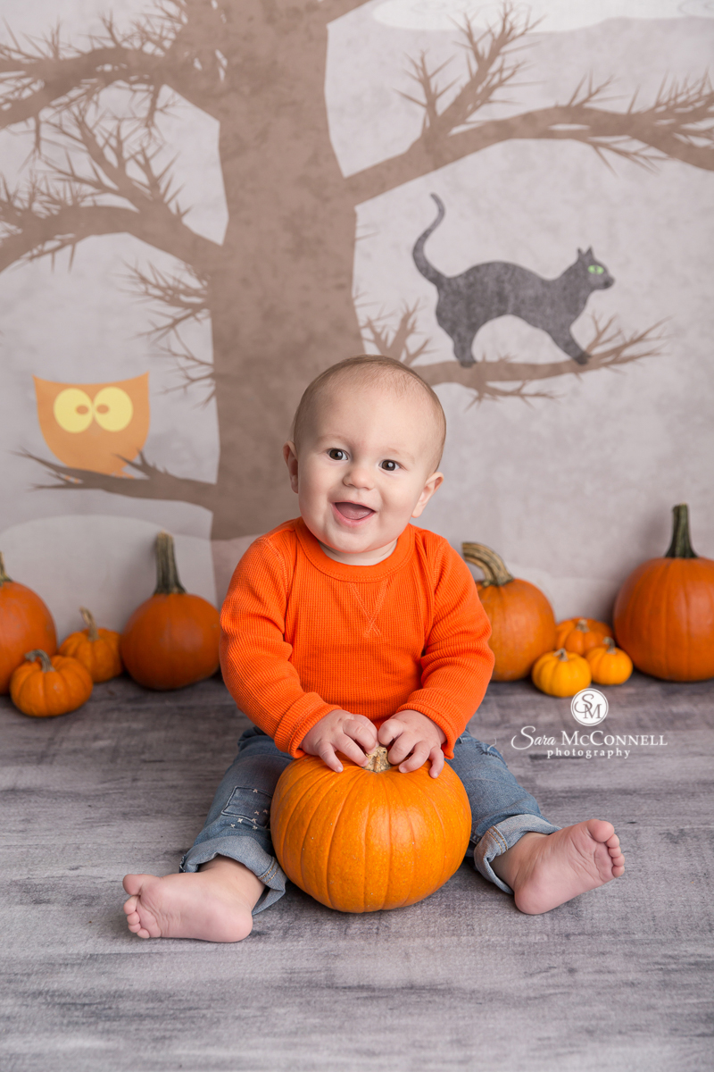 baby holding a pumpking