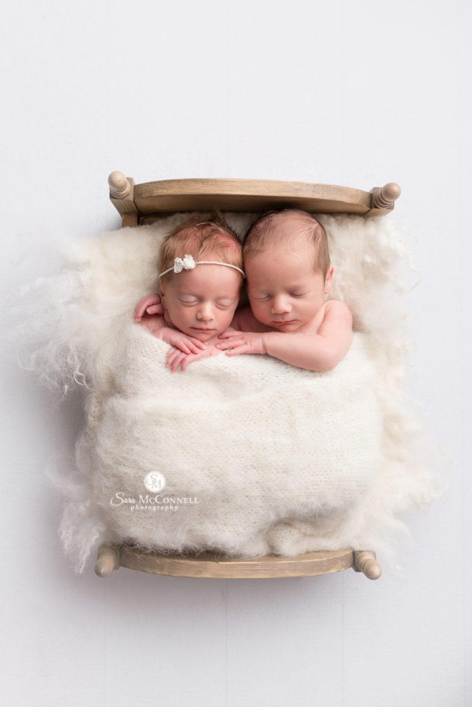 twins in a mini wooden bed wrapped in white