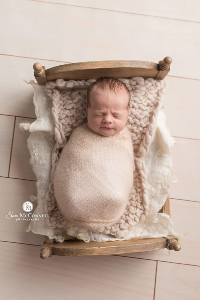 baby wrapped in beige in a wooden bed
