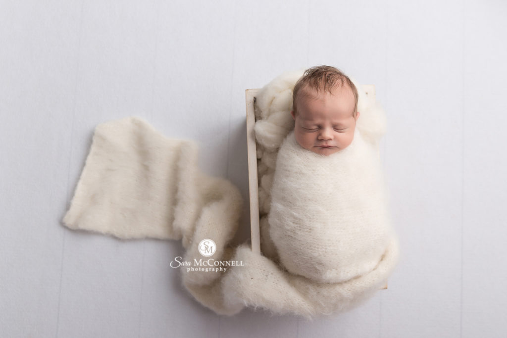 newborn baby wrapped in white