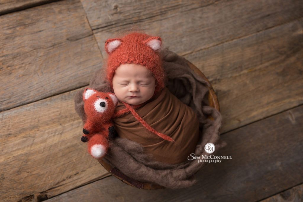 newborn baby wrapped in brown wearing a fox hat