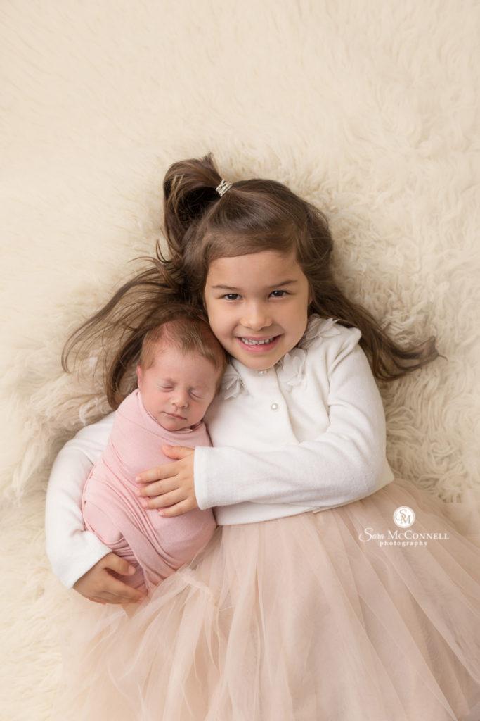 big sister cuddling little sister