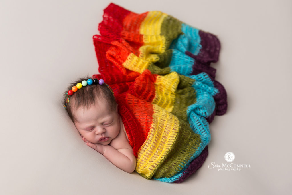 Baby wrapped in rainbow blanket