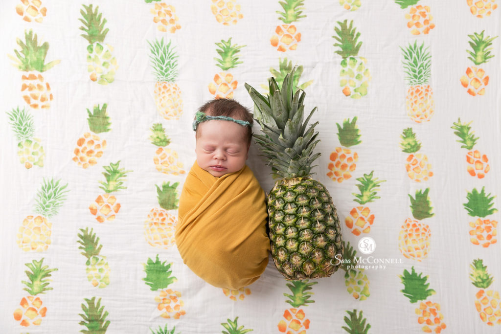 Baby in a yellow wrap with pineapple backdrop for a newborn photo session with Sara McConnell Photography