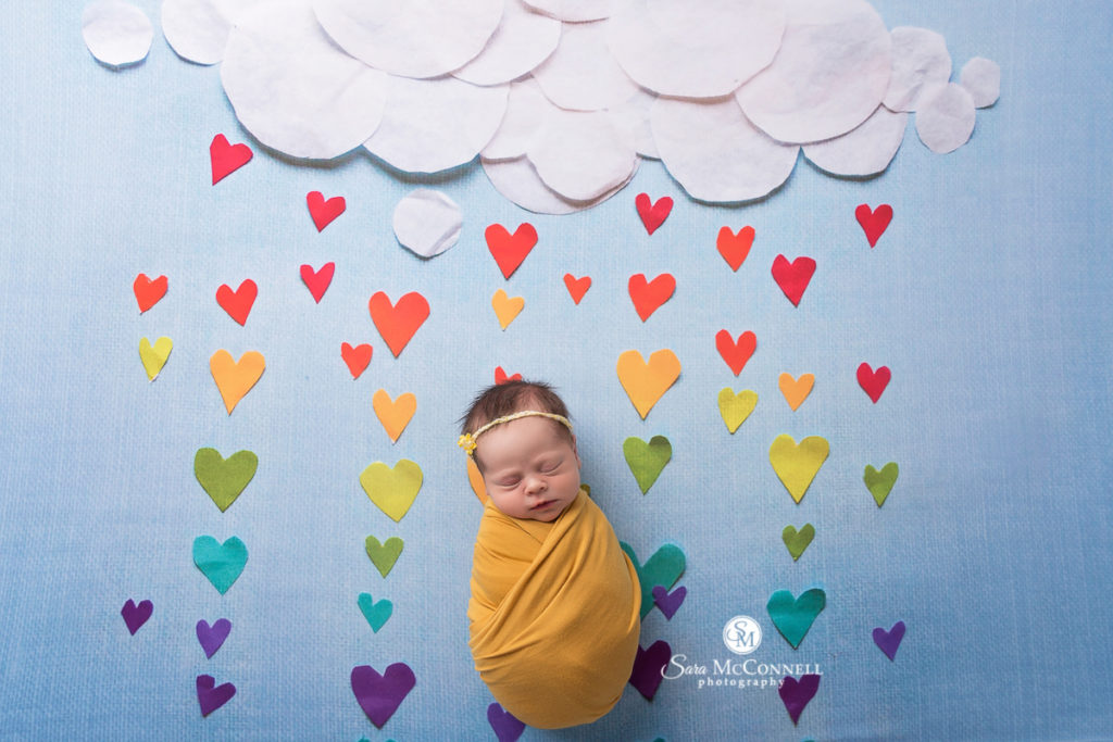 newborn baby wrapped in yellow with a cloud backdrop and raining coloured hearts - newborn photo session with sara mcconnell photography
