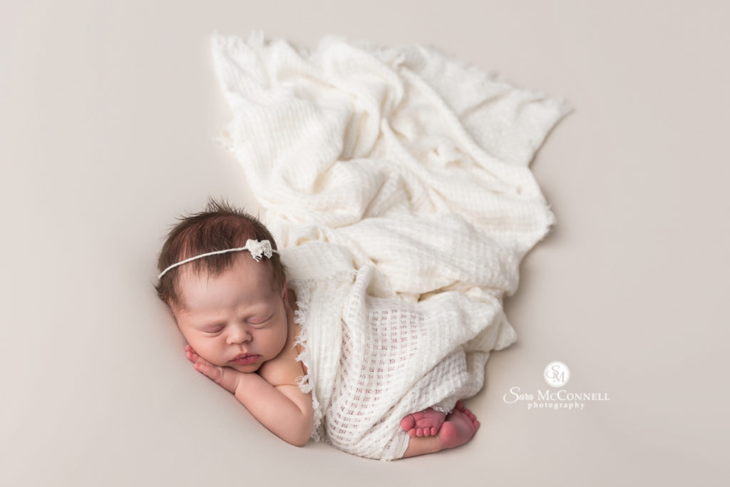 Baby wrapped in white for a newborn photo session with Sara McConnell Photography