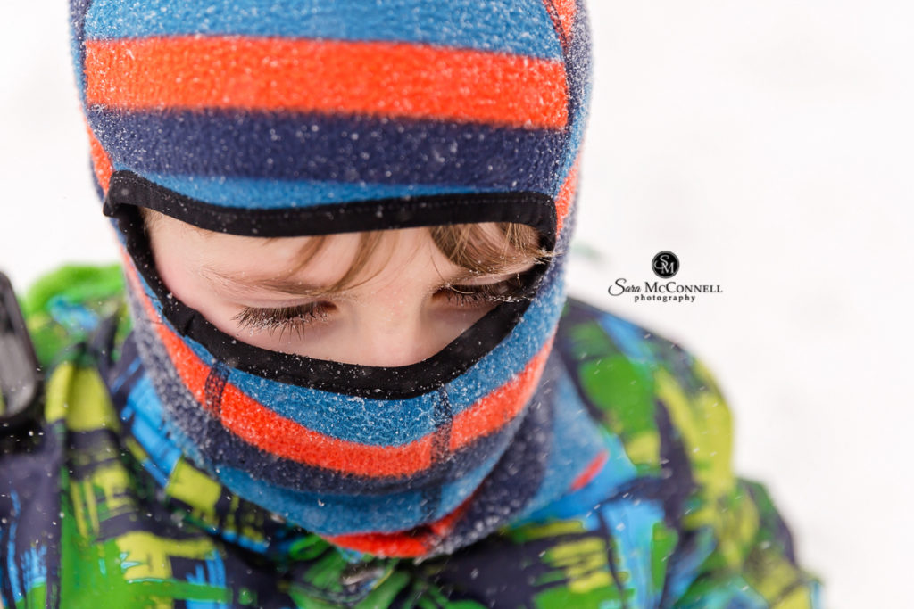 young boy wearing bright coloured winter mask