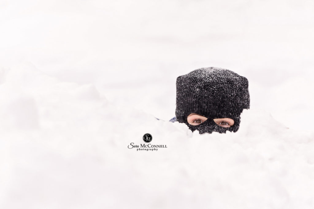 Boy wearing ski mask peeking out of the snow