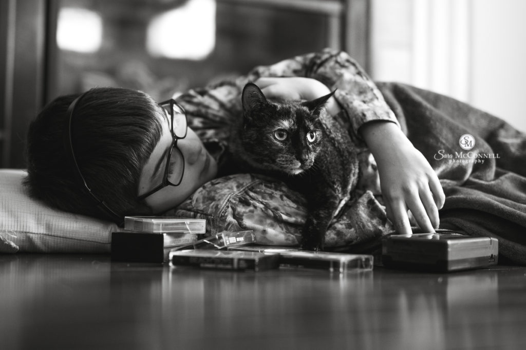 young boy wearing headphones and snuggling his cat