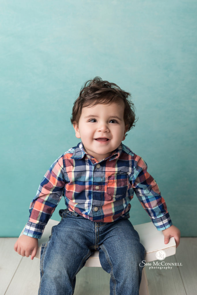 Boy wearing plaid shirt smiling in front of turquoise backdrop - photo by Sara McConnell Photography