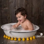 baby in bathtub surrounded by yellow rubber duckies