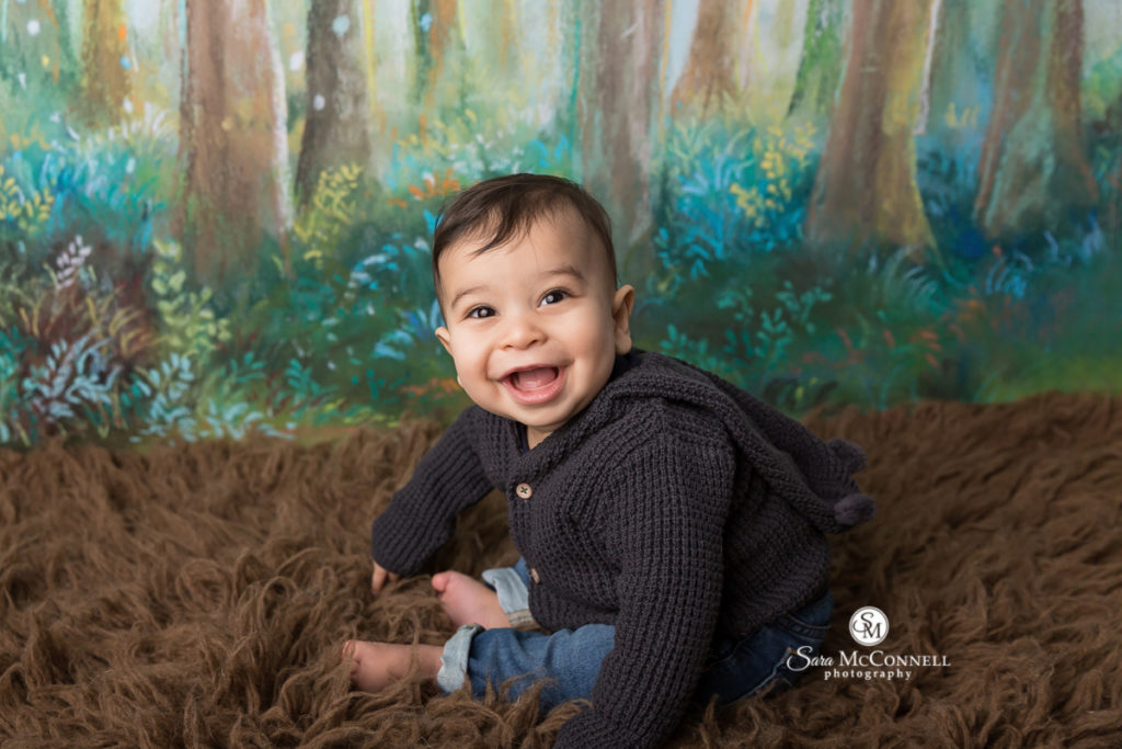 smiling baby boy in front of a woodsy painted backdrop on a brown furry rug