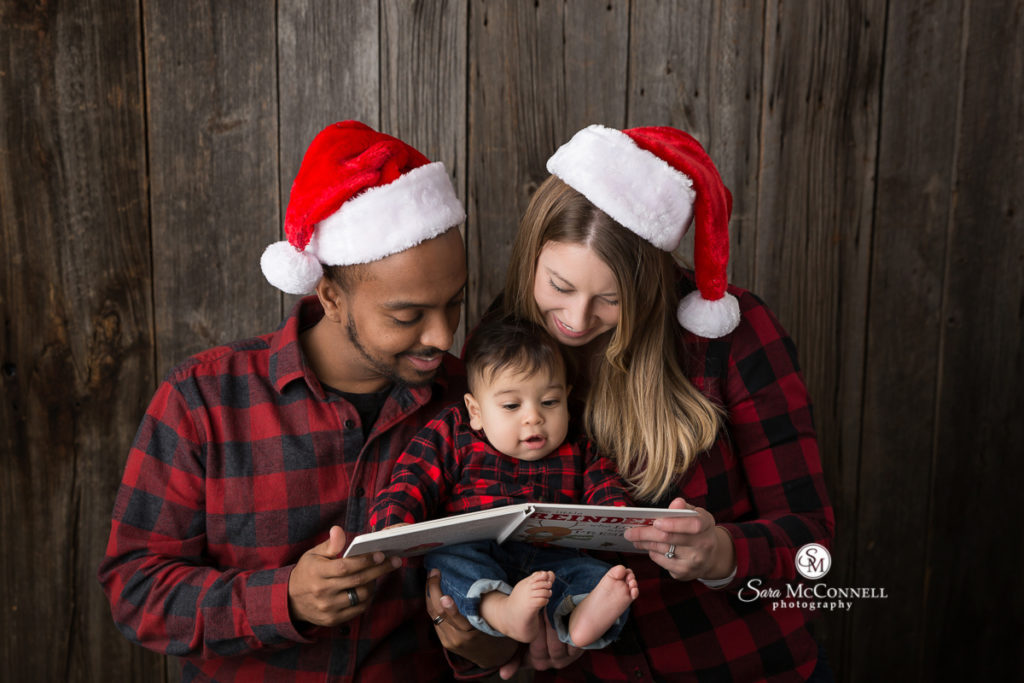 parents reading to baby boy while wearing santa hats