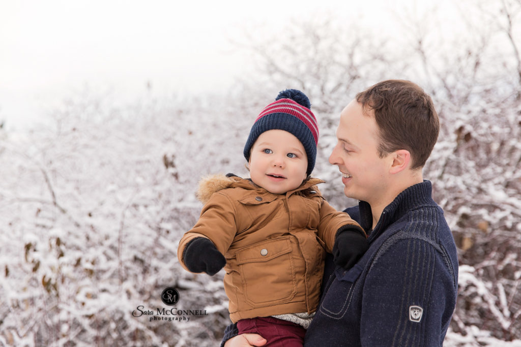 father holding young child in the snow