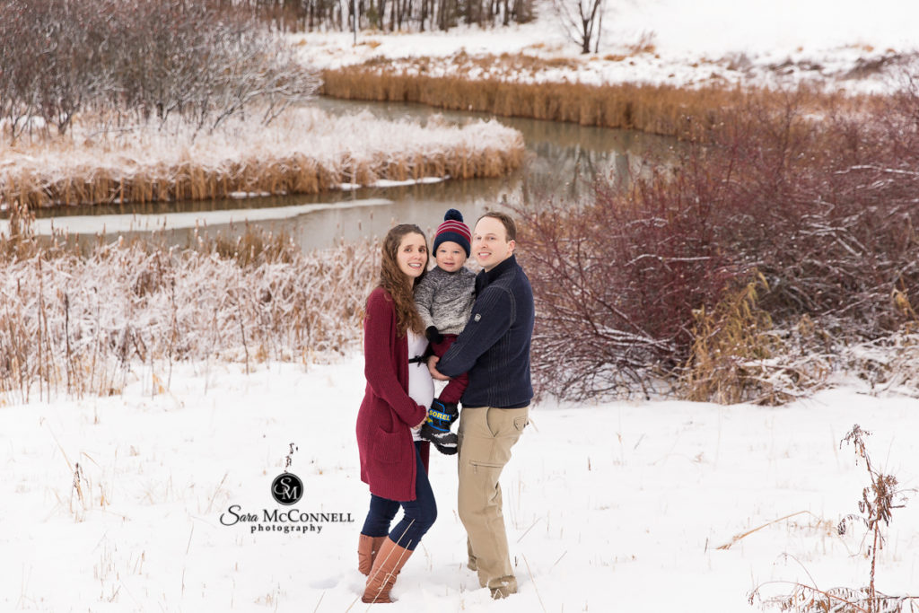 mother, father and child pose in front of stream of water with snow on the ground