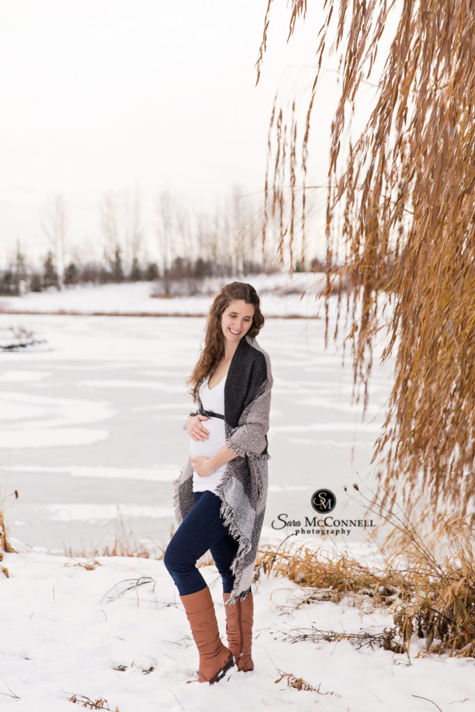 expectant mother holding belly while in the snow