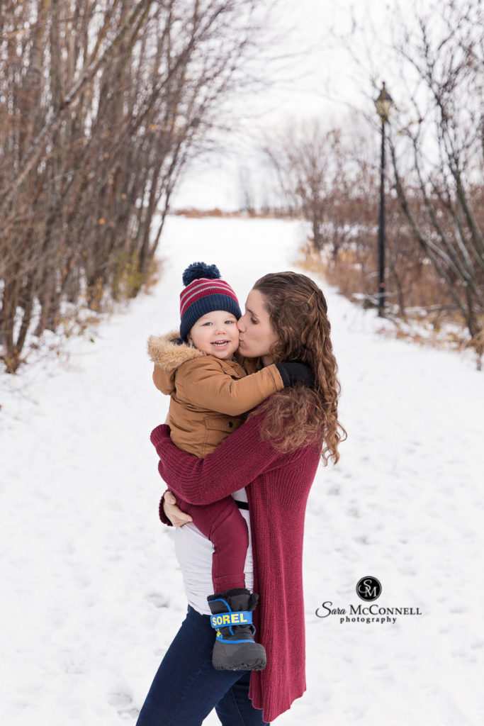 Winter maternity sessions - expectant mother is holding toddler