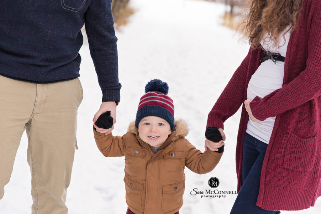 winter maternity session - toddler is holding hands with parents