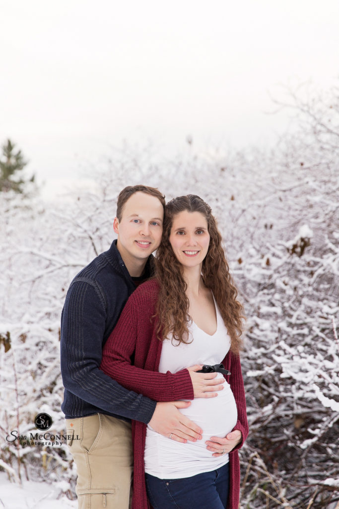 expectant parents posing for winter maternity session