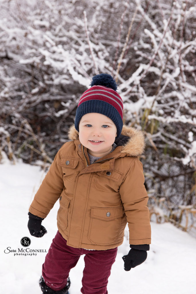 toddler wearing winter jacket and toque in the snow
