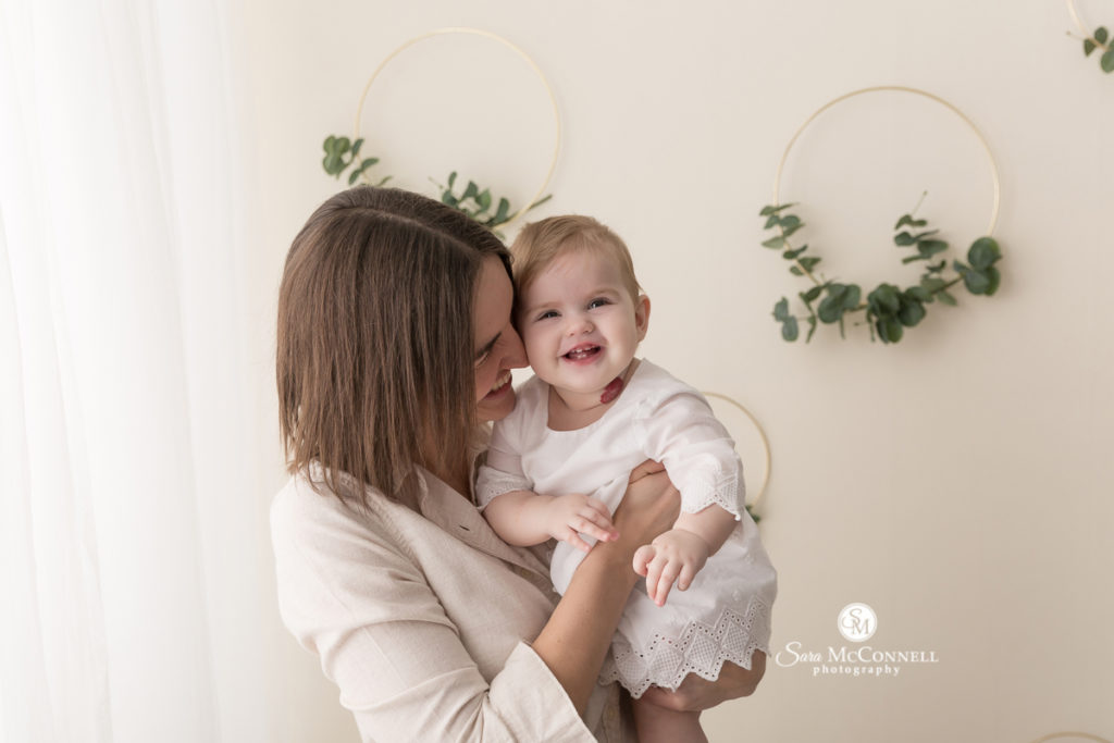 mother holding smiling baby for Mother's Day photos with Sara McConnell Photography