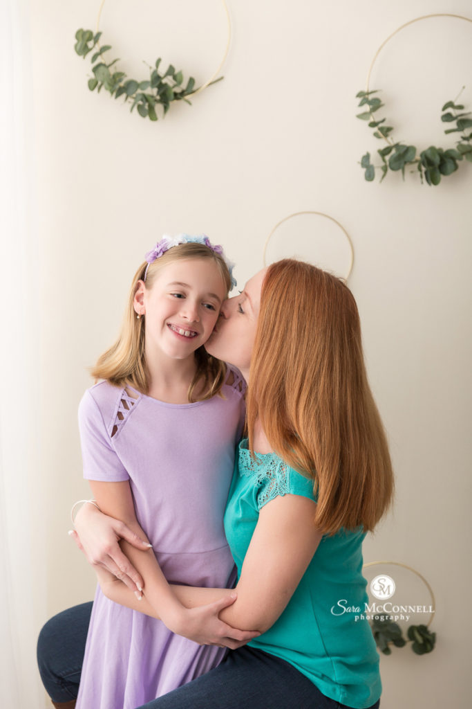 mother kissing daughter on the cheek  for Mother's Day photos with Sara McConnell Photography
