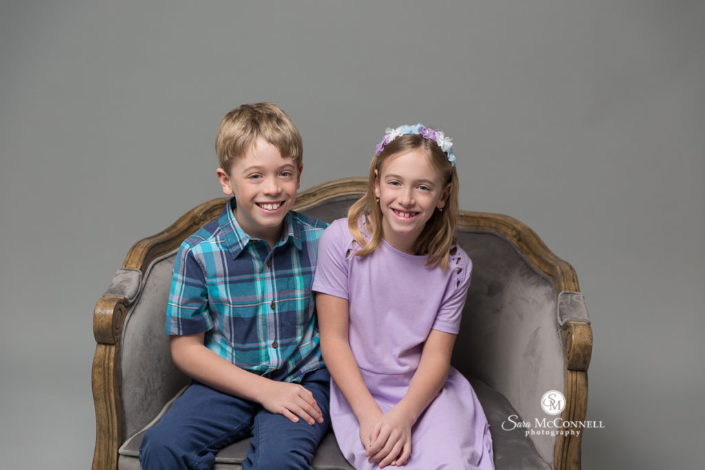 two children sitting in a velvet chair  for Mother's Day photos with Sara McConnell Photography