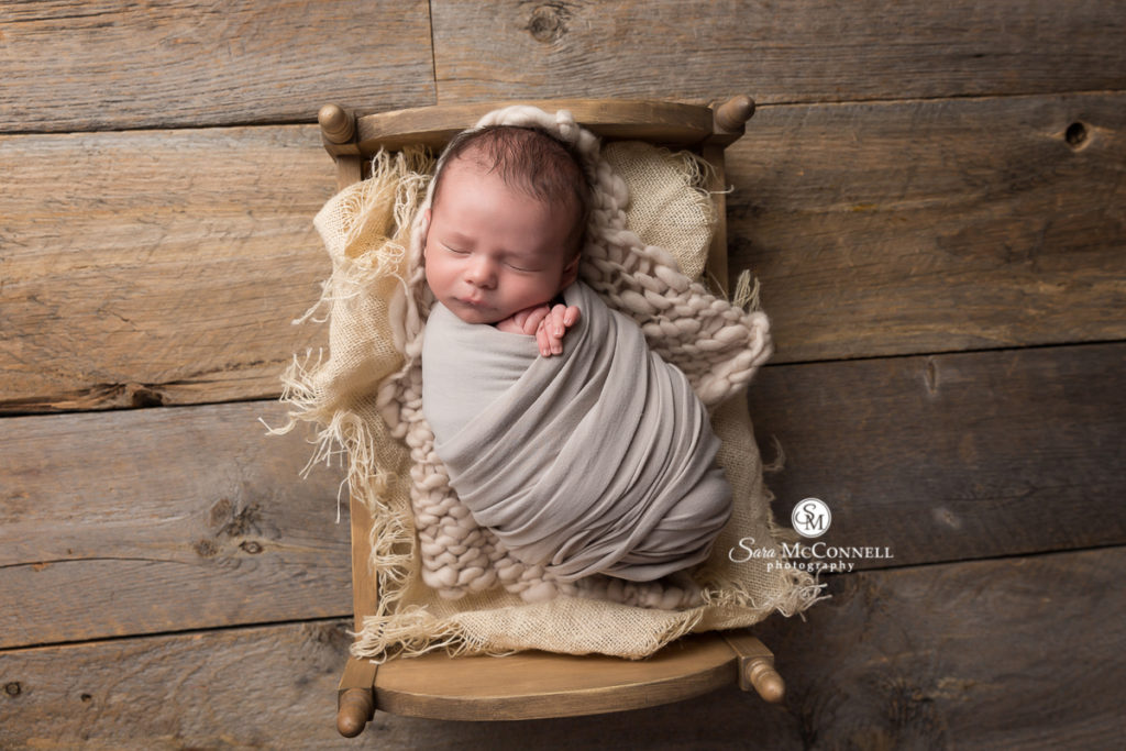 sleeping newborn baby wrapped in grey and sleeping in a wood bed