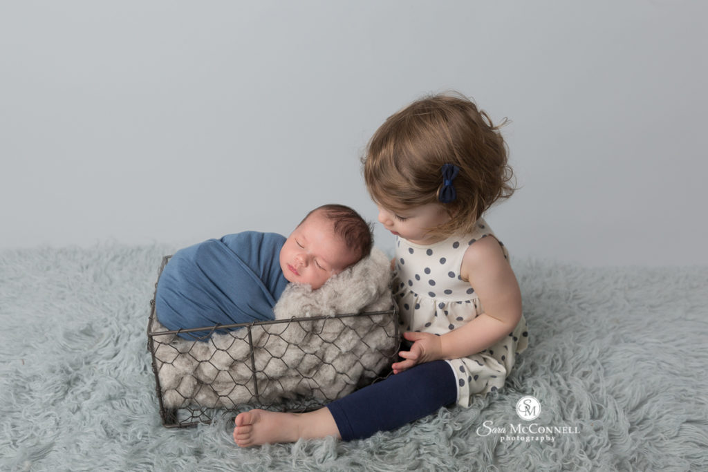 big sister looking at newborn baby brother wrapped in blue