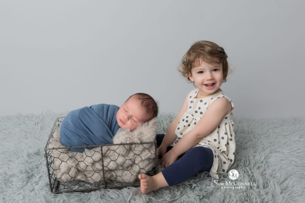 newborn baby sleeps in a wire basket while his big sister smiles