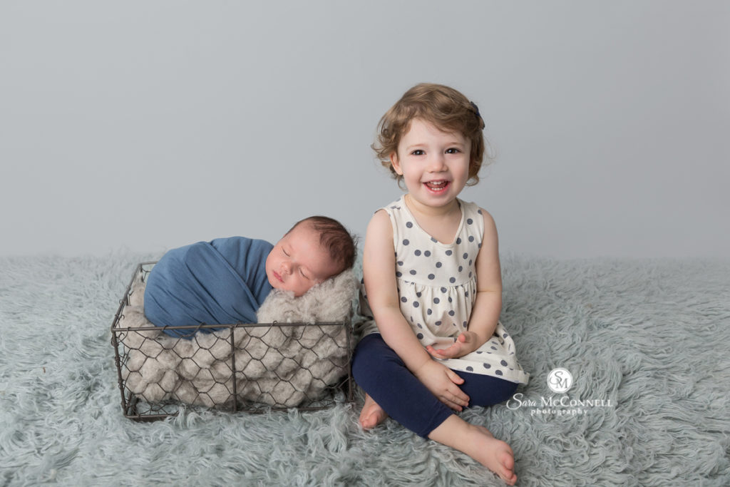 Big sister with newborn baby brother wrapped in blue.