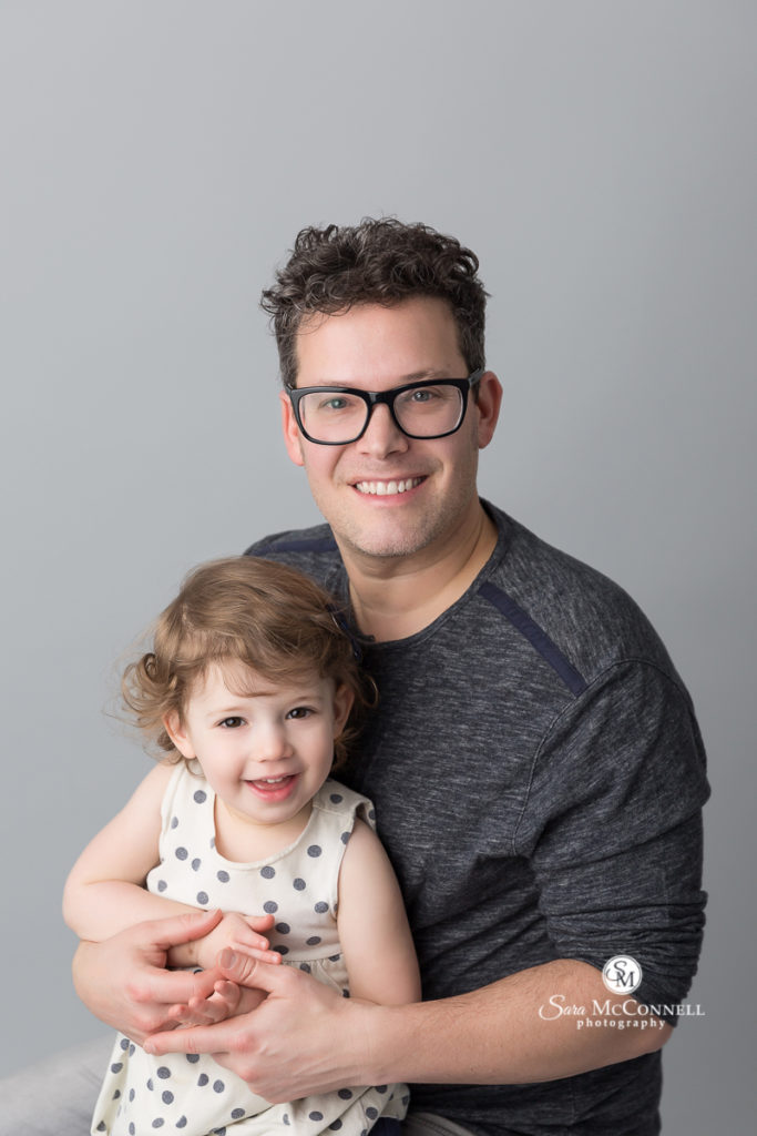 father and toddler girl smiling together