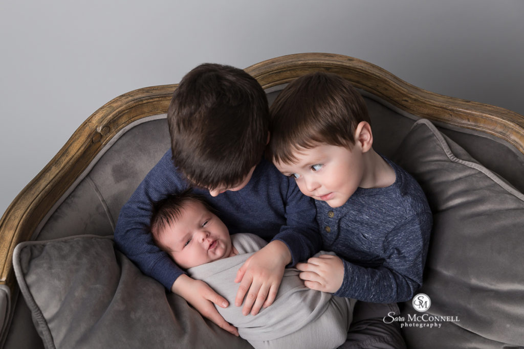 Brothers holding newborn baby