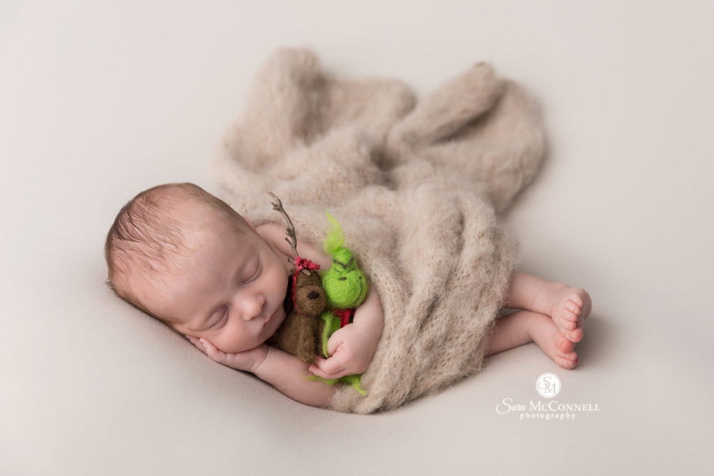 newborn baby sleeping and holding max and grinch stuffies