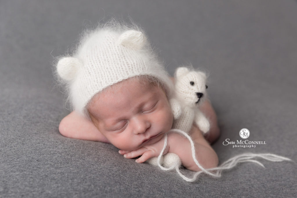 sleeping baby wearing bear hat and holding a stuffed bear