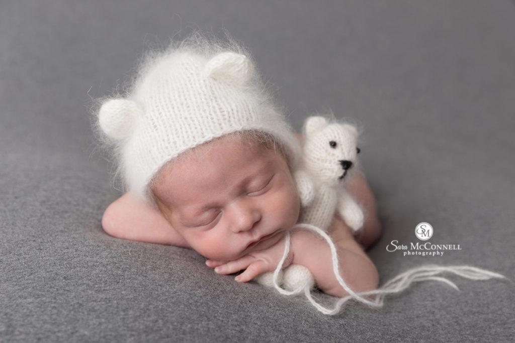 sleeping baby wearing bear hat and holding a stuffed bear