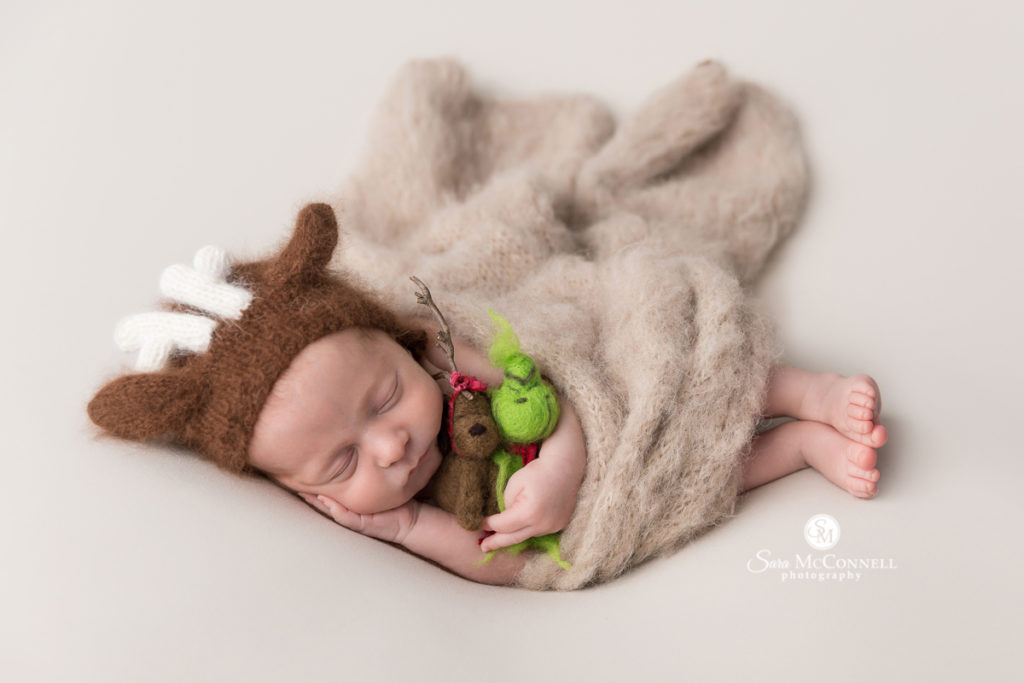 newborn baby wearing reindeer hat and holding grinch and max stuffies