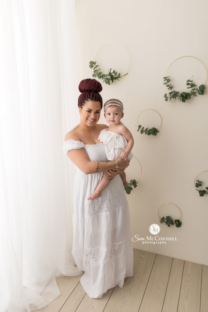 mother wearing white gown holding daughter wearing white gown