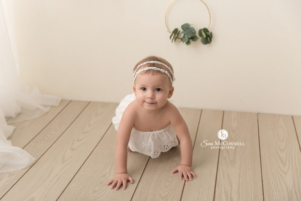 baby crawling on the floor while wearing a white dress and headband