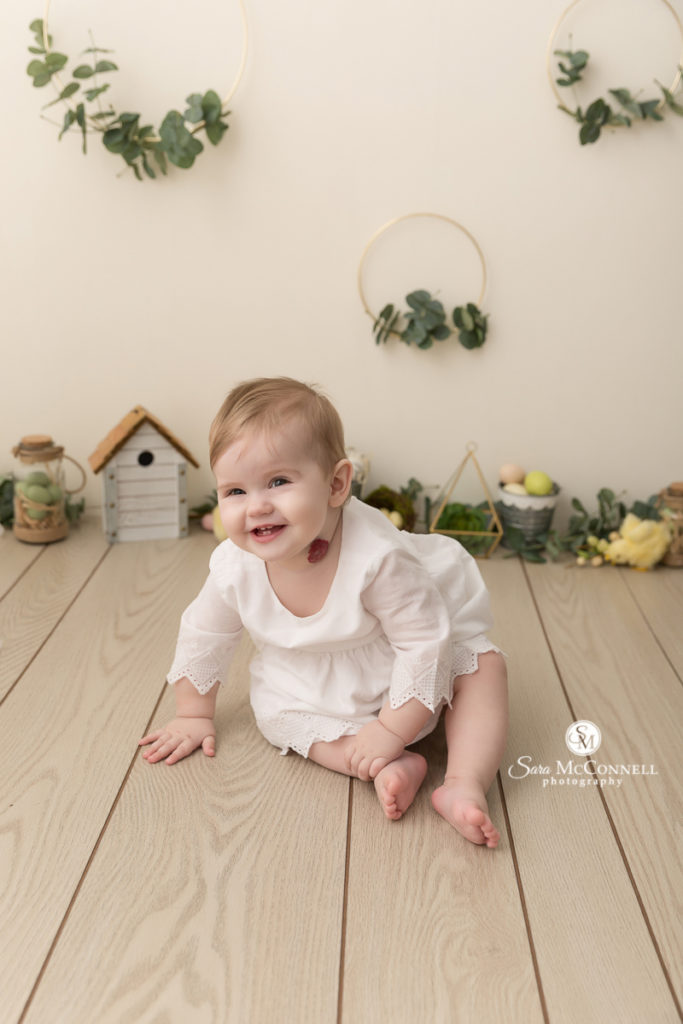 baby smiling in front of greenery and spring decor