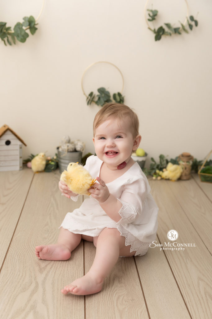 baby smiling in front of greenery and spring decor while holding a pretend baby chick