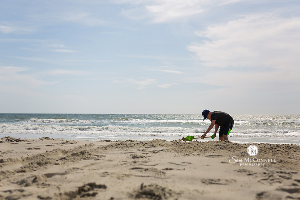 young boy playing in the sand in front of the water
