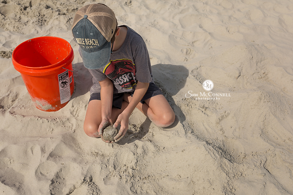 young boy digging in the sand