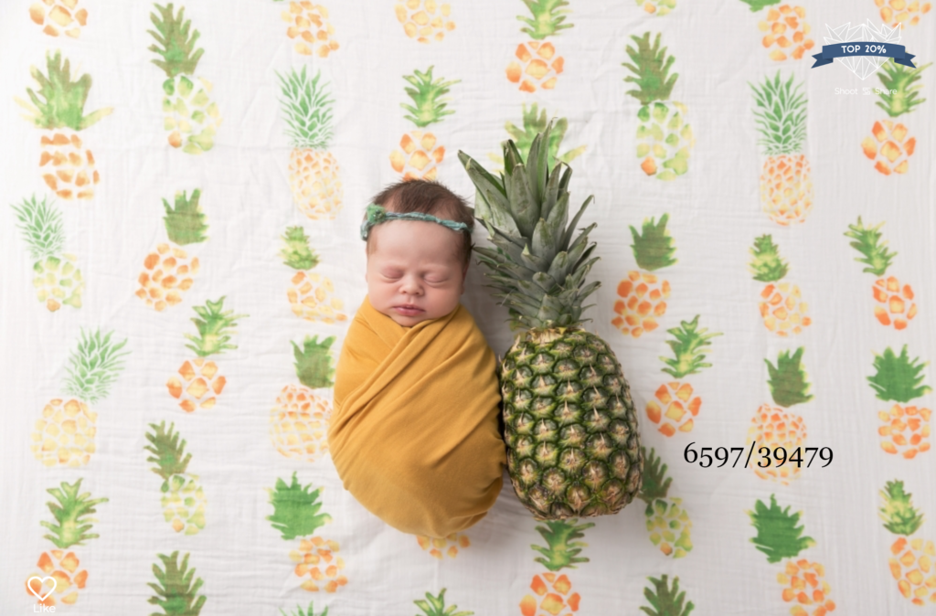 baby wrapped in yellow against a yellow backdrop beside a yellow pineapple