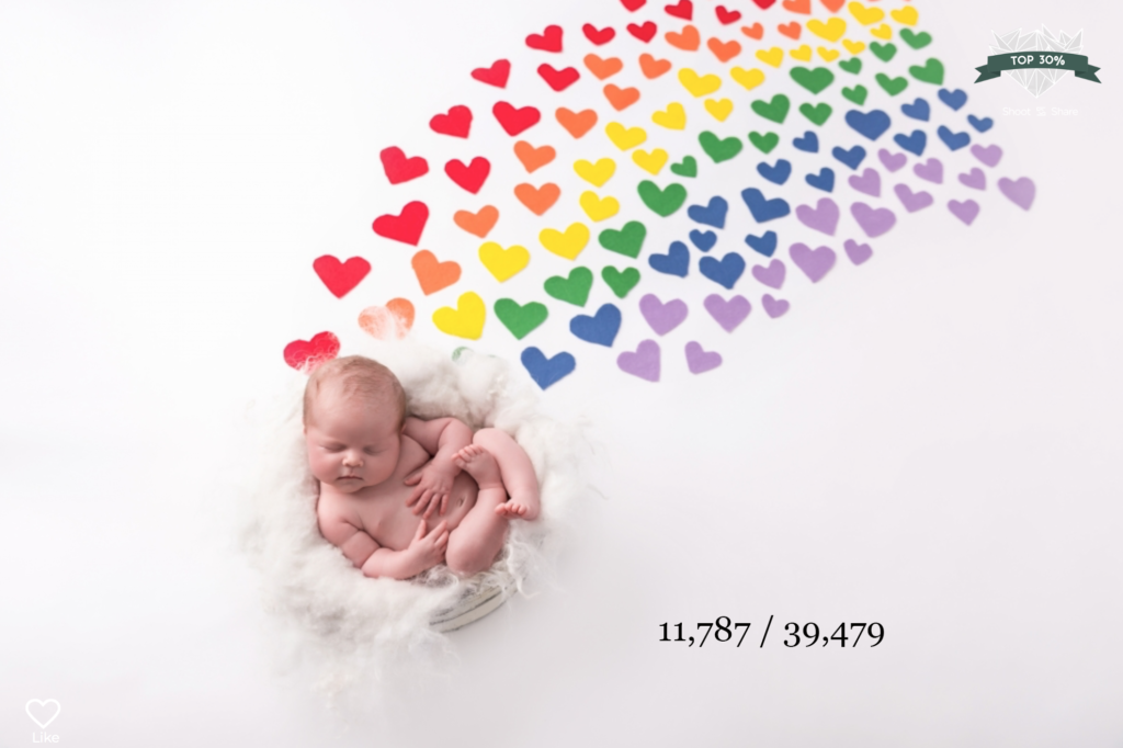 baby sleeping with colourful rainbow hearts