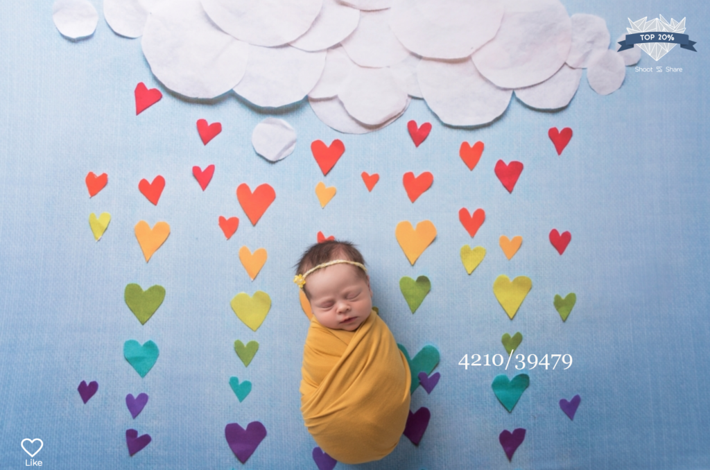 baby wrapped in yellow with a cloud and colourful hearts raining down